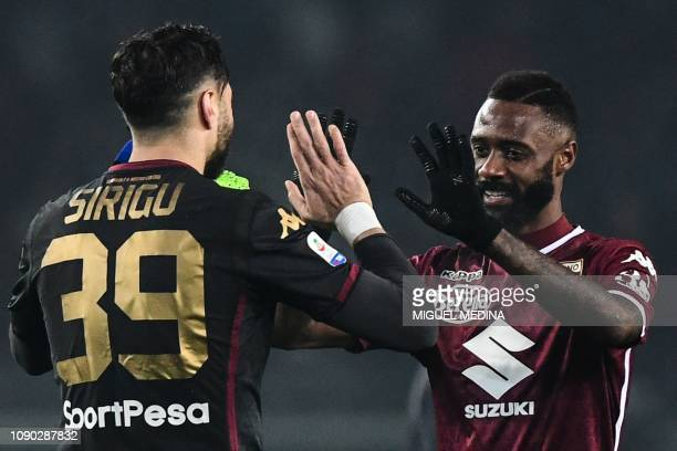 Torino's Italian goalkeeper Salvatore Sirigu and Torino's Cameroonian defender Nicolas Nkoulou tap hands at the end of the Italian Serie A football...