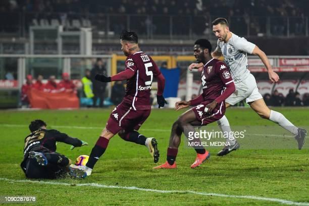 Torino's Italian goalkeeper Salvatore Sirigu covered by Torino's Italian defender Armando Izzo and Torino's Nigerian defender Ola Aina dives to grab...