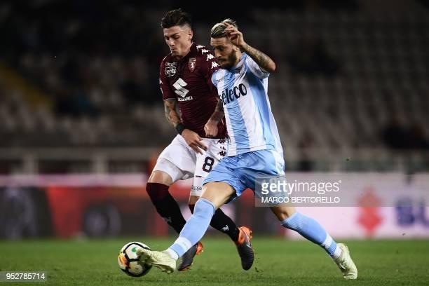 Torino's Italian midfielder Daniele Baselli fights for the ball with Lazio's Spanish forward Luis Alberto Romero Alconchel during the Italian Serie A...