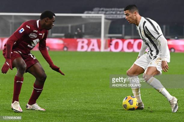 Torino's Ivorian defender Wilfried Singo fights for the ball with Juventus' Portuguese forward Cristiano Ronaldo during the Italian Serie A football...