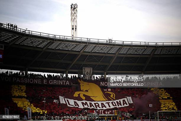 Torino's supporters hold a giant banner as they cheer for their team during the Italian Serie A football match between Torino and Juventus at the...