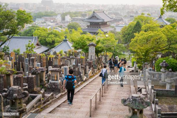 Torists walking trought cemetery in foreground and Kyoto city urban sprawl in background