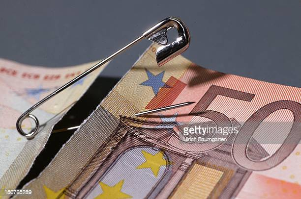 Torn 50 Euro banknote is being fixed by a safety pin