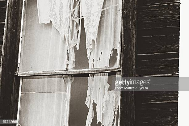 torn curtain hanging at window of abandoned building - steve matten stock pictures, royalty-free photos & images