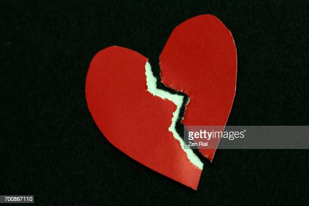 torn heart shaped paper on black background - broken heart stock pictures, royalty-free photos & images