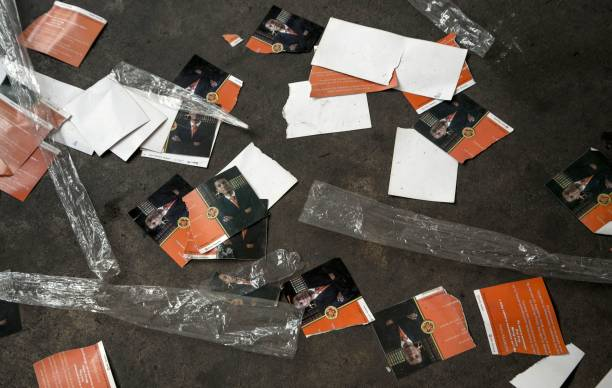 torn invitation cards lie on the ground ahead of the first political