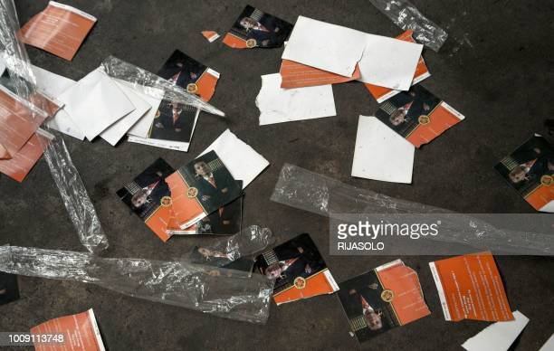 Torn invitation cards lie on the ground ahead of the first political meeting of Andry Rajoelina, former President of the High Transitional Authority...