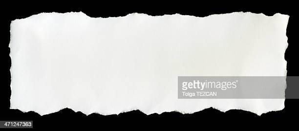 A torn piece of white paper on a black background