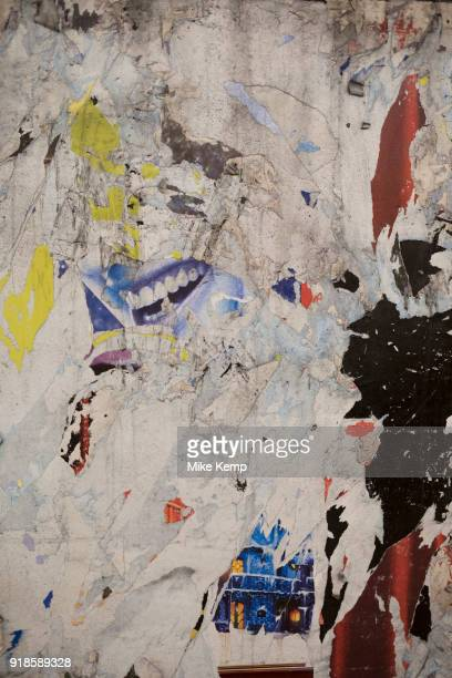 Torn posters on an underground station wall in London, England, United Kingdom.