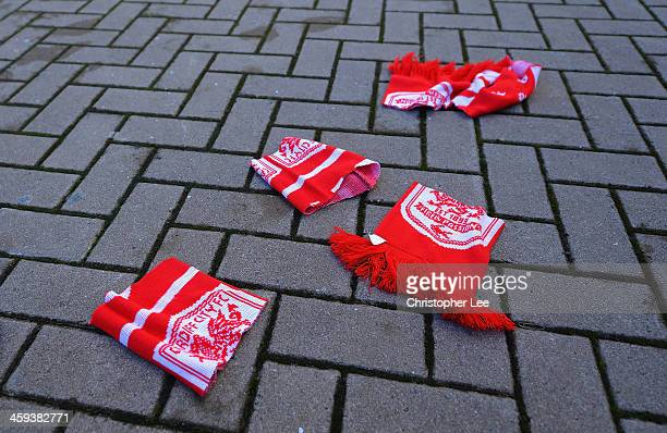 Torn red Cardiff City scarves are pictured on the floor outside the ground prior to the Barclays Premier League match between Cardiff City and...
