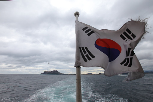 Torn South Korea flag on ferry, with Ilchulbong volcanic crater seen in the background - gettyimageskorea