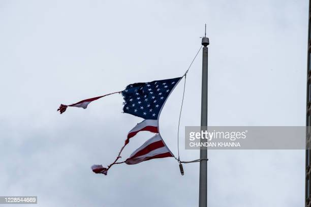Torn US national flag is seen during Hurricane Sally landfall in Mobile, Alabama on September 16, 2020. - Hurricane Sally barrelled into the US Gulf...