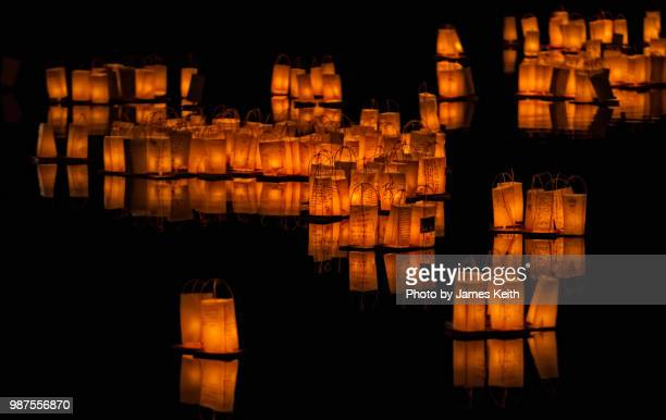 toro nagashi is a long-held japanese tradition where candle-lit lanterns are released into rivers to guide the spirits of ancestors back to the other world during the obon season. - ボン ストックフォトと画像