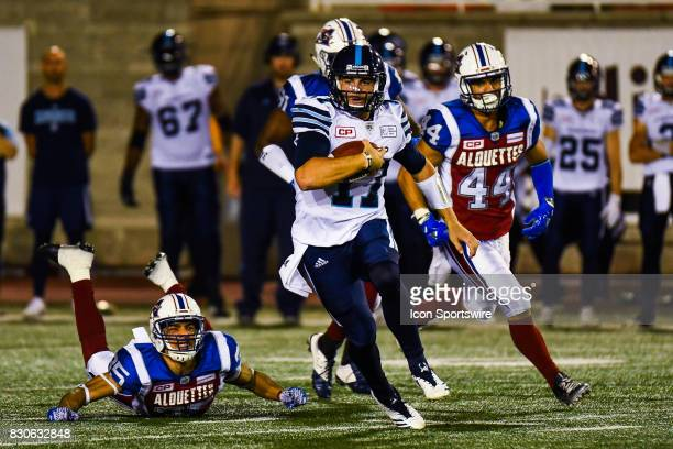 Toronto Argonauts quarterback Cody Fajardo running with the ball leaving Montreal Alouettes defensive back Jalen Rogers on the ground during the...