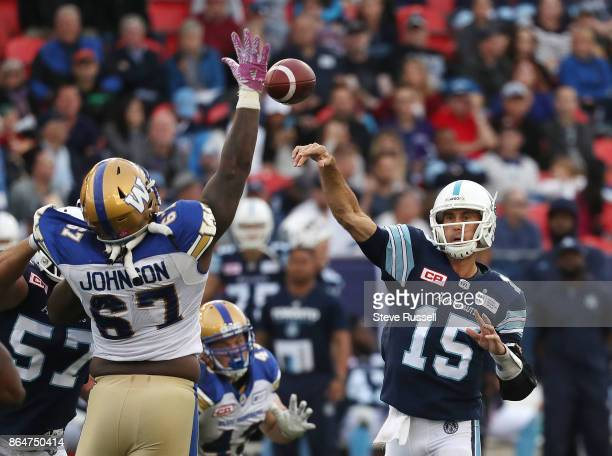 TORONTO ON OCTOBER 21 Toronto Argonauts quarterback Ricky Ray throws past Winnipeg Blue Bombers defensive tackle Cory Johnson as the Toronto...
