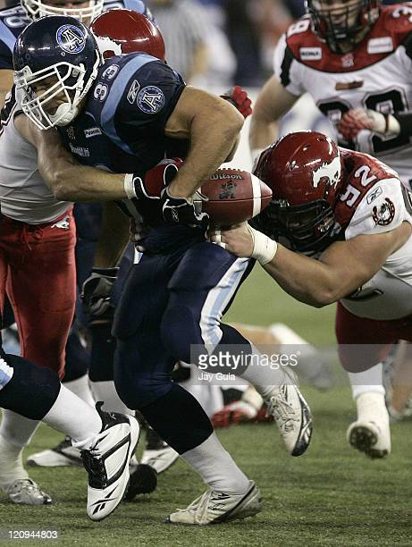 Toronto Argonauts RB Jeff Johnson loses the football while fighting off Calgary Stampeder tacklers in CFL action at Rogers Centre in Toronto, Canada....