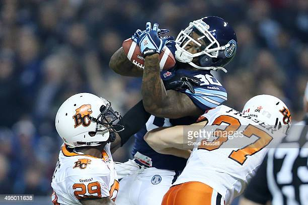 Toronto Argonauts wide receiver Phil Bates gets up over BC Lions defensive back Steven Clarke and BC Lions defensive back Eric Fraser to score a...