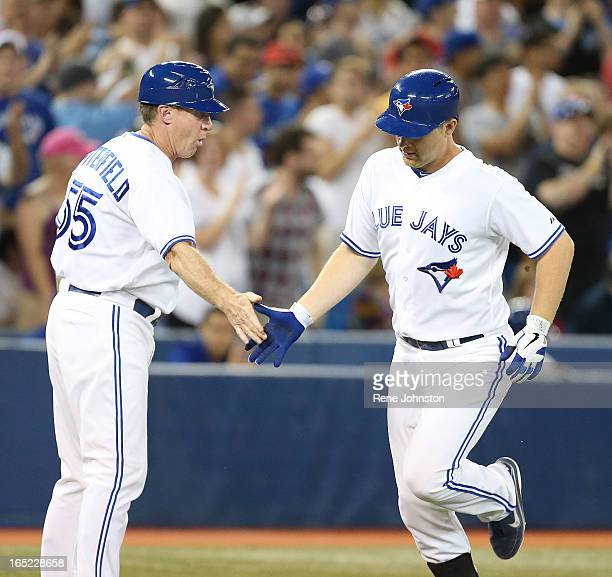 Toronto Blue Jay and recent call up Adam Lind is welcomed home by Brian Butterfield at third after he hit his second homer of the night to put the...