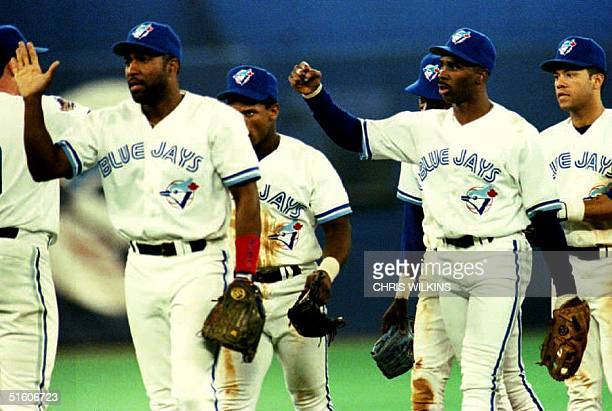 Toronto Blue Jay Devon White and his teammates celebrate late 16 October 1993 their victory against the Philadelphia Phillies 85 in game one of the...