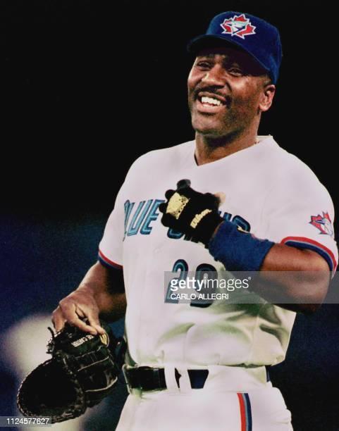 Toronto Blue Jay first baseman Joe Carter laughs while talking to first base umpire Joe Brinkman in the sixth inning at Toronto's Skydome 06 May With...