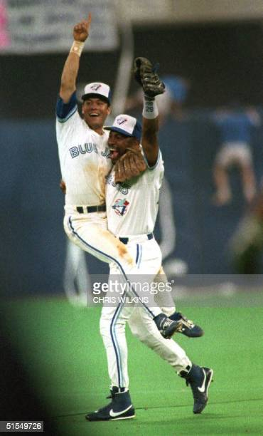 Toronto Blue Jay Roberto Alomar jumps into the arms of Joe Carter after winning game six of the American League Championship Series against the...