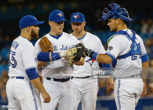 Toronto Blue Jays 3rd baseman Russell Martin and Toronto Blue Jays catcher Luke Maile mid five gloves just before Toronto Blue Jays relief pitcher...