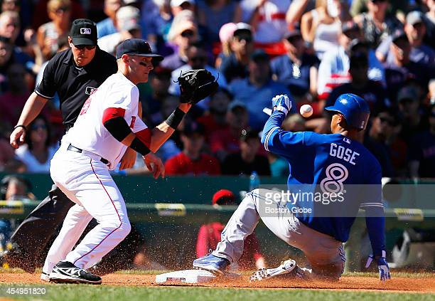 Toronto Blue Jays Anthony Gose right slides safely into third in front of Red Sox Will Middlebrooks during the fifth inning of play at Fenway Park in...