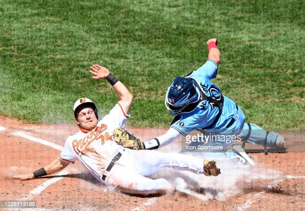 Toronto Blue Jays catcher Reese McGuire tags Baltimore Orioles shortstop Pat Valaika out at home plate in the fourth inning on August 19 at Orioles...