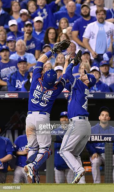 Toronto Blue Jays catcher Russell Martin and third baseman Josh Donaldson battle to catch a pop up by the Kansas City Royals' Kendrys Morales to end...