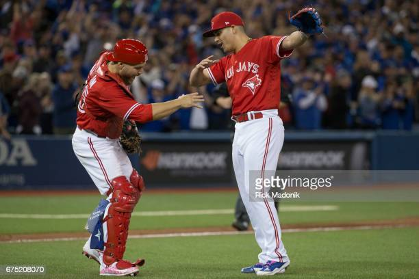 Toronto Blue Jays catcher Russell Martin and Toronto Blue Jays relief pitcher Roberto Osuna do a little celebratory routine following the victory...