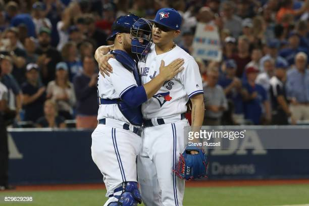 TORONTO ON AUGUST 10 Toronto Blue Jays catcher Russell Martin and Toronto Blue Jays relief pitcher Roberto Osuna embrace after recording the final...