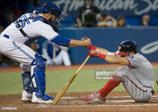 Toronto Blue Jays catcher Russell Martin gives Washington Nationals center fielder Adam Eaton a hand up after he ended up in the dirt in the batter's...