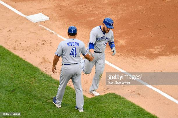 Toronto Blue Jays catcher Russell Martin high fives Toronto Blue Jays third base coach Luis Rivera after hitting a home run against the Chicago White...