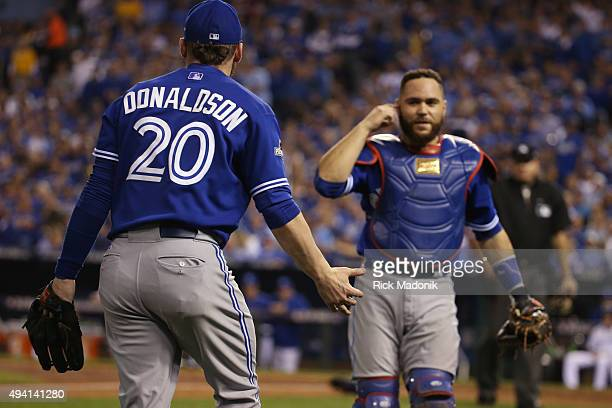 Toronto Blue Jays catcher Russell Martin motions to Toronto Blue Jays third baseman Josh Donaldson asking if he heard him call for a pop up ball in...