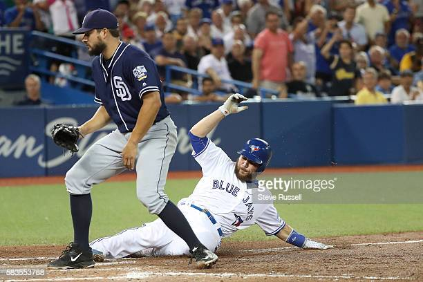 Toronto Blue Jays catcher Russell Martin scores the tying run as the Toronto Blue Jays play the San Diego Padres at the Rogers Centre in Toronto....