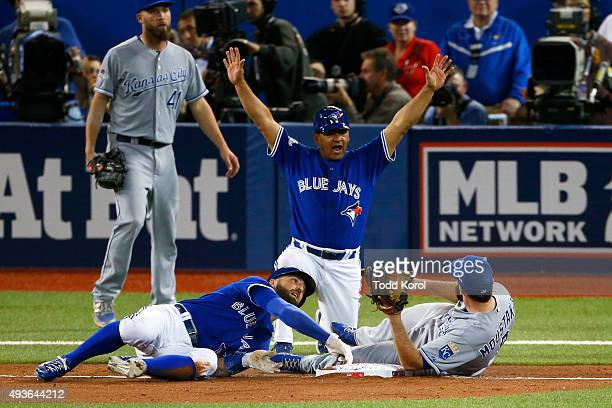 Toronto Blue Jays center fielder Kevin Pillar tags the third base while Kansas City Royals third baseman Mike Moustakas stays on the bag for the out...