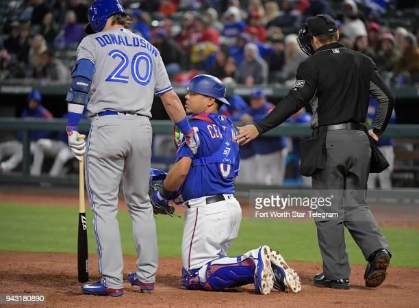 Toronto Blue Jays designated hitter Josh Donaldson and umpire Mark Wegner steady Texas Rangers catcher Juan Centeno after he was hit by a foul tip...