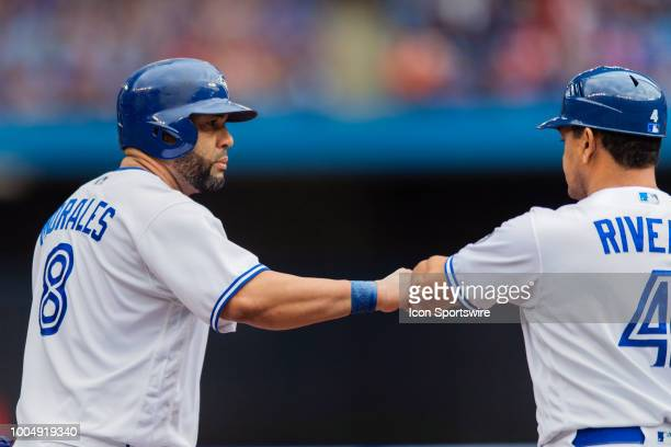 Toronto Blue Jays Designated hitter Kendrys Morales is congratulated on his hit by teammate Third base Coach Luis Rivera during the MLB game between...