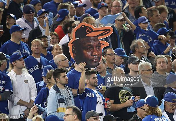 Toronto Blue Jays fan holds up a cardboard cutout of the crying Michael Jordan meme before the start of the game against the Baltimore Orioles in the...