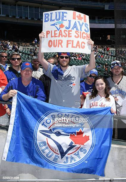 Toronto Blue Jays fans hold up a sign and flag prior to the game against the Detroit Tigers at Comerica Park on June 8 2016 in Detroit Michigan The...