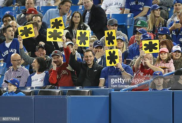 Toronto Blue Jays fans hold up asterisk cards during MLB game action as Alex Rodriguez of the New York Yankees bats on April 14 2016 at Rogers Centre...