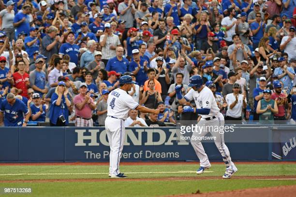 Toronto Blue Jays First base Justin Smoak celebrates a two run homer with third base coach Luis Rivera during the regular season MLB game between the...