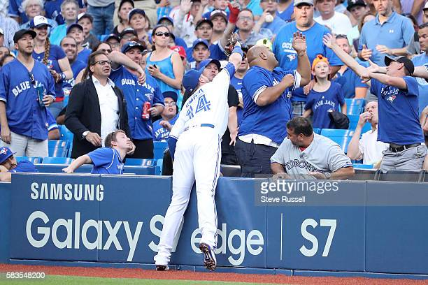 TORONTO ON JULY 26 Toronto Blue Jays first baseman Justin Smoak goes after a ball in the stands as the Toronto Blue Jays play the San Diego Padres at...