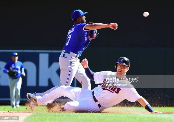 Toronto Blue Jays Infield Richard Urena throws over a sliding Minnesota Twins First base Joe Mauer during a MLB game between the Minnesota Twins and...