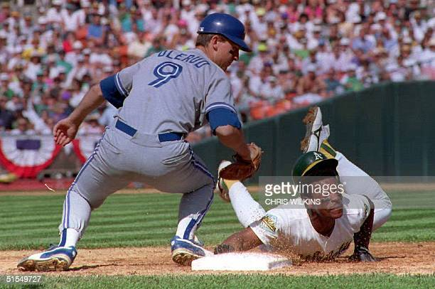 Toronto Blue Jays John Olerud tries to tag out Oakland A's Rickey Henderson in a pick-off attempt at first base 12 October, 1992 in the third inning...