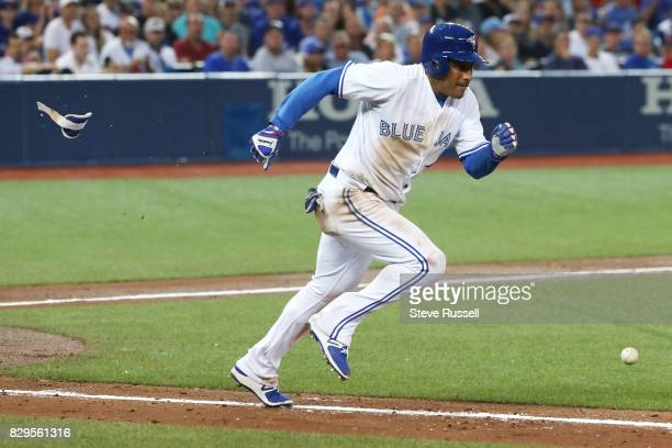 TORONTO ON AUGUST 10 Toronto Blue Jays left fielder Ezequiel Carrera loses equipment as he tries to leg out a bunt moving the runner on base over as...