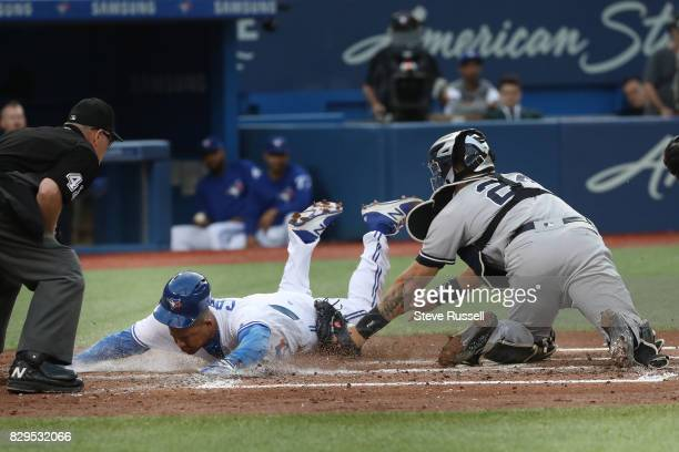 TORONTO ON AUGUST 10 Toronto Blue Jays left fielder Ezequiel Carrera opens the scoring sliding past Gary Sanchez on a Ryan Goins infield hit as the...