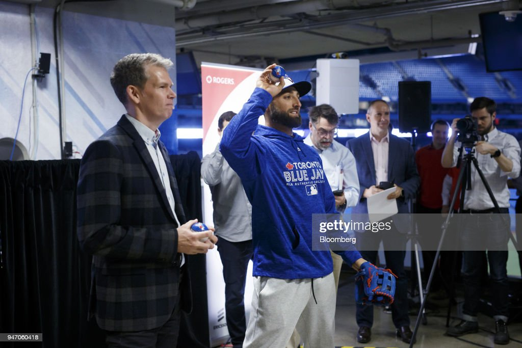 Toronto Blue Jays outfielder Kevin Pillar, center, throws a baseball to a Rogers Communications Inc. employee wearing a virtual reality (VR) headset during a demonstration of 5G wireless network technology in Toronto, Ontario, Canada, on Monday, April 16, 2018. Chief Technology Officer Jorge Fernandes said that 5G networks probably won't to be ready for prime time until about 2020 while hardware and software is developed. Photographer: Cole Burston/Bloomberg via Getty Images