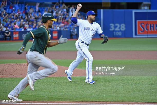 Toronto Blue Jays Pitcher Cesar Valdez throws over to first base ahead of Oakland Athletics Shortstop Marcus Semien during the MLB regular season...
