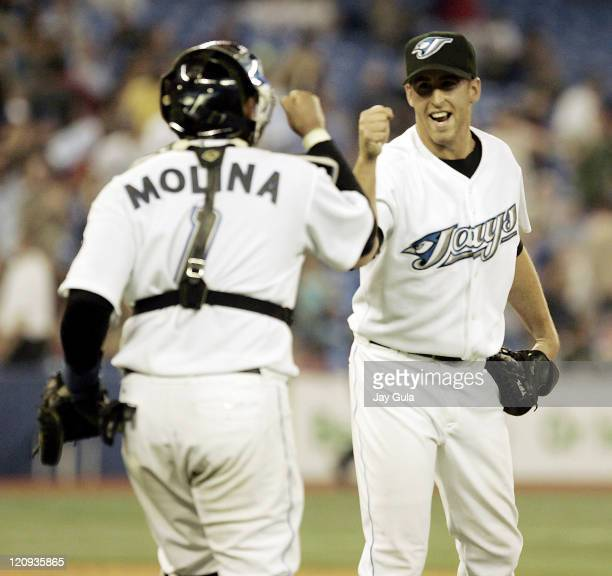 Toronto Blue Jays pitcher Vinnie Chulk high fives with Bengie Molina after the Blue Jays defeated the Texas Rangers 101 in MLB action at Rogers...
